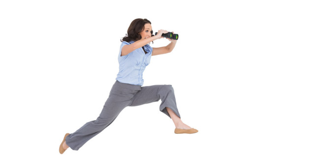 Cheerful classy businesswoman on white background jumping while holding binoculars