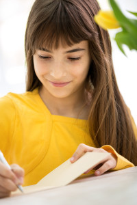 beautiful girl writes greeting card